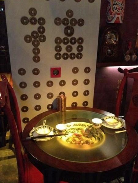 北京老家採用舊式的實木枱椅,牆上掛滿清朝時的將軍圖畫,大紅燈籠、京劇面譜等,營造老北京風格(網上圖片)