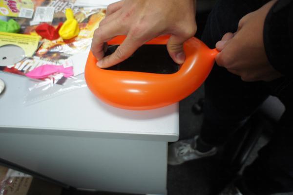 再把手機放在氣球的中心,一手按住吹口,一手把手機往下壓