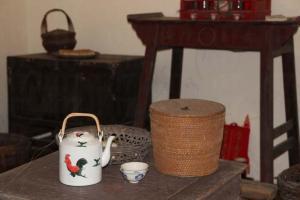 在正廳的木桌上,擺放著充滿農家味道的公雞茶壺和茶點。