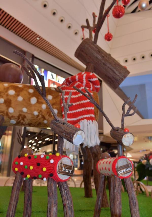 多隻以原木製成的馴鹿套上冬日暖暖毛衣或鮮艷冷頸巾