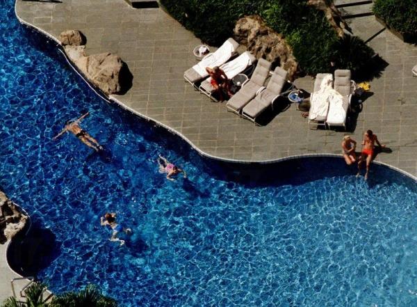 旅客在酒店泳池悠閒的暢泳。