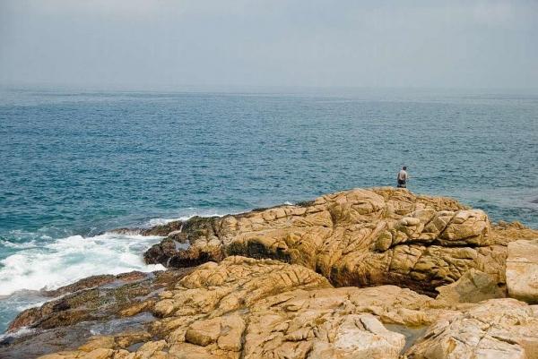 釣友在巨石上釣魚。