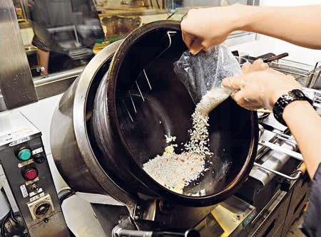 麵店的獨門炒飯機,放蛋和飯後,高溫極速炒飯,以攝氏 240 度將飯粒炒香,而其螺旋傾斜設計可減少炒飯時水份流失。(麵座)