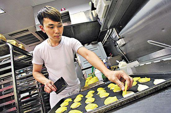 阿良每天晨早 5 時回到麵包店,便開始做麵包,採訪期間剛製造菠蘿包,在包面放上「菠蘿皮」,隨後便放入焗爐。