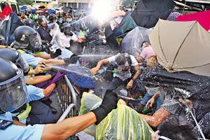 警方使用胡椒噴霧驅趕示威者,有示威者穿上雨衣及以雨傘遮擋。