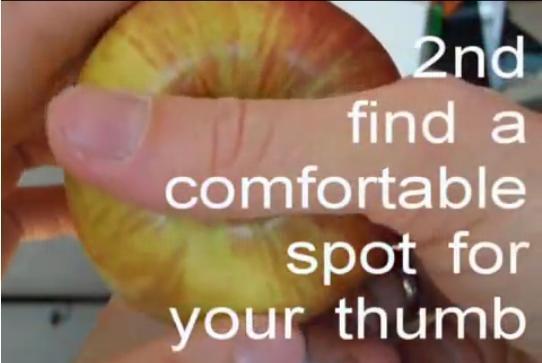 步驟2:把2隻手指公放在蘋果中間凹陷的位置