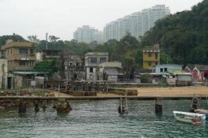 人去樓空的懷舊漁村,背景是一排豪宅屏風樓,形成強烈對比。