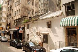 藏身於唐樓群的百年客家石屋,黑瓦白屋與兩旁灰牆唐樓形成有趣鮮明對比。