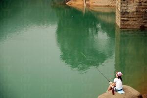 湖邊遊人在旁悠然自得釣魚。