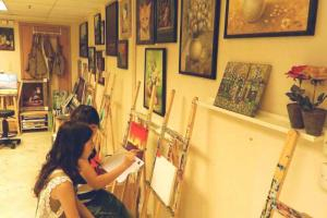 導師 Cammy 正在教導學生塑膠彩繪畫的筆法。