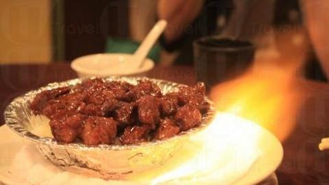 黑椒牛柳粒置於滲了火酒的鹽上,上桌時一點火,極盡娛樂性。(關璇攝)