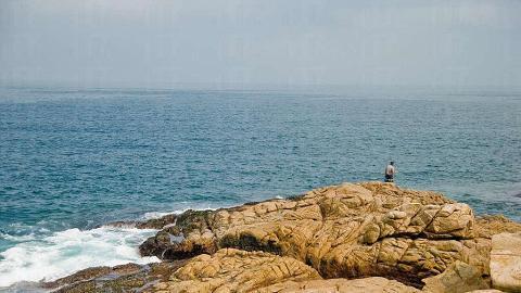 釣友在巨石上釣魚,面對巨浪拍岸,需要與大海角力。