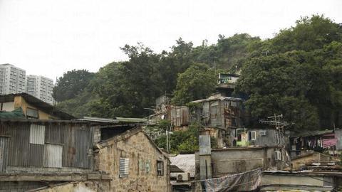 依山而建的茶果嶺混合了百年客家村落的石屋和怱忙建成的鐵皮屋。