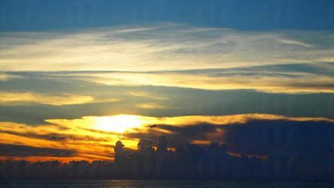 日落為天空和海面添上一抹金黃,襯托遠方的飛機份外迷人。