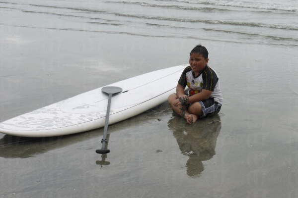 玩過滑浪板後,小朋友累得索性坐下休息。